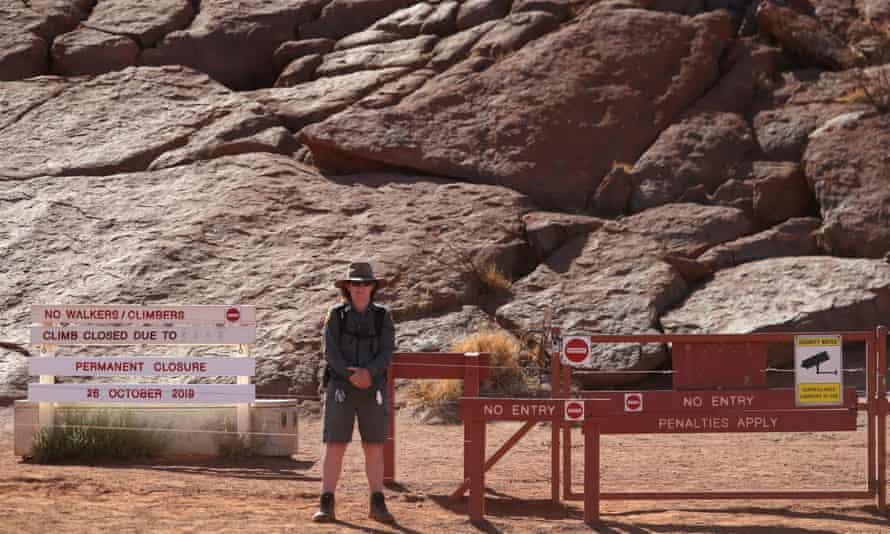 A ranger stands guard at the base of the climb at Uluru.
