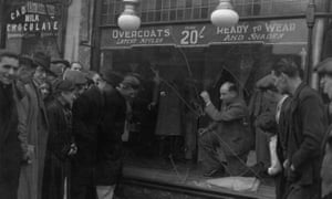 People inspect the damage to a clothing shop window smashed by anti-semitic gangs in east London in 1936