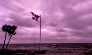 An American flag battered by Hurricane Michael continues to fly in the in the purple colored light of sunset at Shell Point Beach on October 10, 2018 in Crawfordville, Florida.