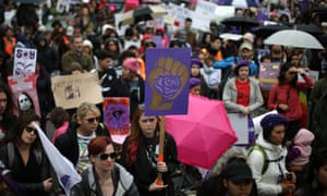 People listen to speakers in the rain at an International Women's Day in Los Angeles, California
