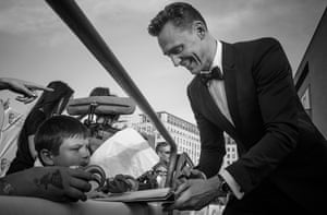 Tom Hiddleston signing a young fan's Loki toy and drawing