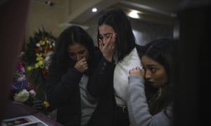 Mourners of Marbella Valdez grieve over her casket during her wake at a funeral home in Tijuana on 14 February.