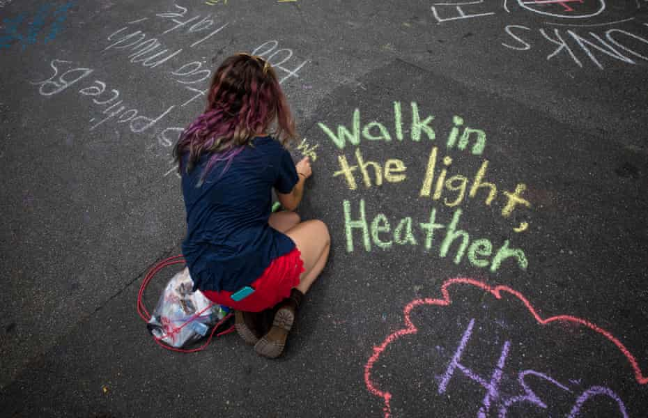 A woman writes messages in chalk in memory of Heather Heyer in Charlottesville, Virginia.