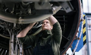 A female engineer works on a jet engine