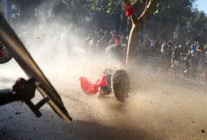 A demonstrator takes cover behind a makeshift shield during an anti-government protest in Santiago, Chile, 15 November