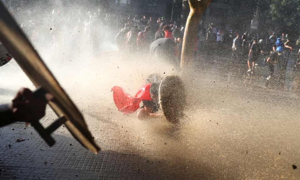 A demonstrator takes cover behind a makeshift shield during a protest in Santiago, Chile, 15 November