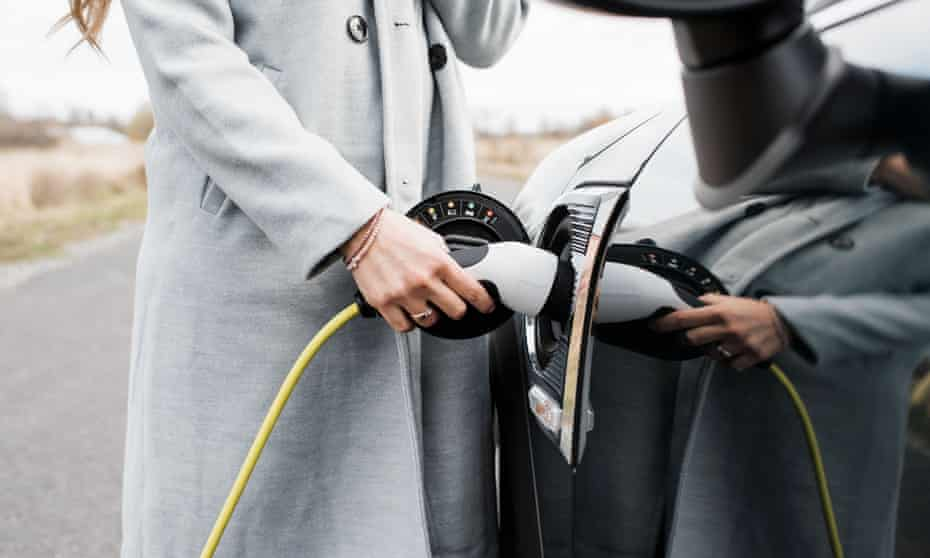 Woman plugging electric charging lead into car