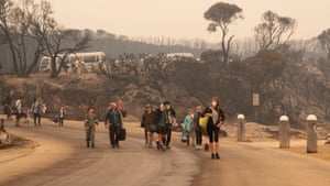 People walk to a beach before being evacuated from Mallacoota, Victoria