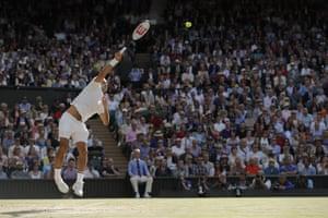 Roger Federer serves.
