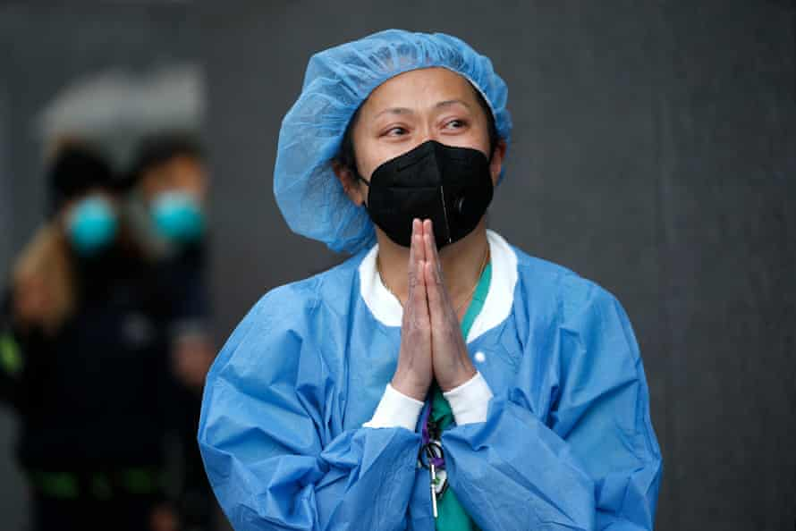 A nurse stands outside NYU Langone hospital in New York.
