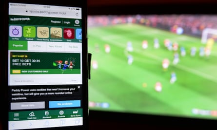 A phone user accesses the Paddy Power website while watching football