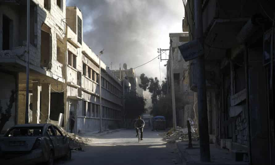 A cyclist amid the rubble in Douma, east of Damascus, following a reported air strike by Syrian government forces