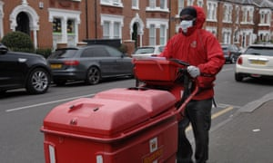 A Royal Mail worker wears an anti-coronavirus face mask and protective gloves