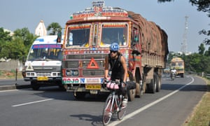 Buhring cycling on a main road in India, with a lorry on her tail