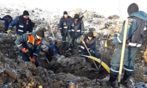 Emergency workers search through the wreckage of the Antonov An-148 that crashed on Sunday outside  Moscow