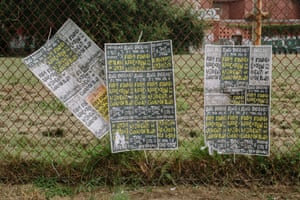 Signs calling for fully-funded relocation support for the residents of Gordon Plaza hang on the fence surrounding Morton elementary school, which sits empty and covered in graffiti.