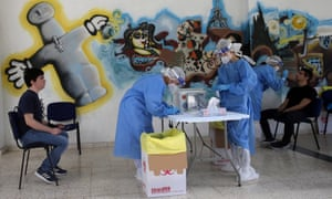 Health workers wear protective gear while collecting nasopharyngeal swab samples from senior high school students in Nicosia, Cyprus, 13 May 2020.