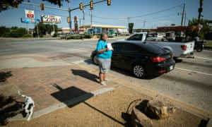 """Becky Blackmon, 54 and homeless, panhandles with a sign reading """"need help"""" at an intersection in Oklahoma City."""