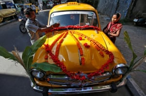 A taxi driver and his wife offer prayers during Vishwakarma Puja, the festival of the Hindu deity of architecture and machinery in Kolkata, India
