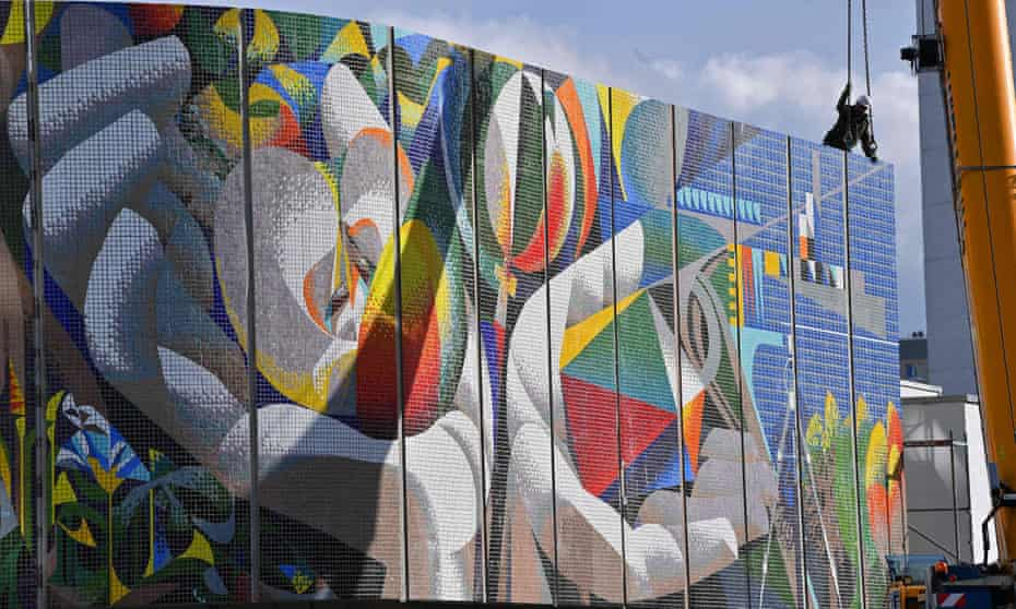 A man works on the assembly of the restored mural, Man's Relation to Nature and Technology, by the Spanish artist Josep Renau in Erfurt, eastern Germany