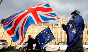 An anti-Brexit demonstrator waves a UK flag alongside a European Union flag outside the Houses of Parliament