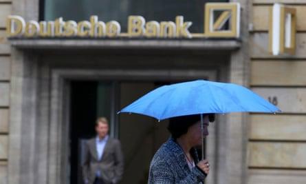 A woman with umbrella walks past a Deutsche Bank branch in Frankfurt on Friday