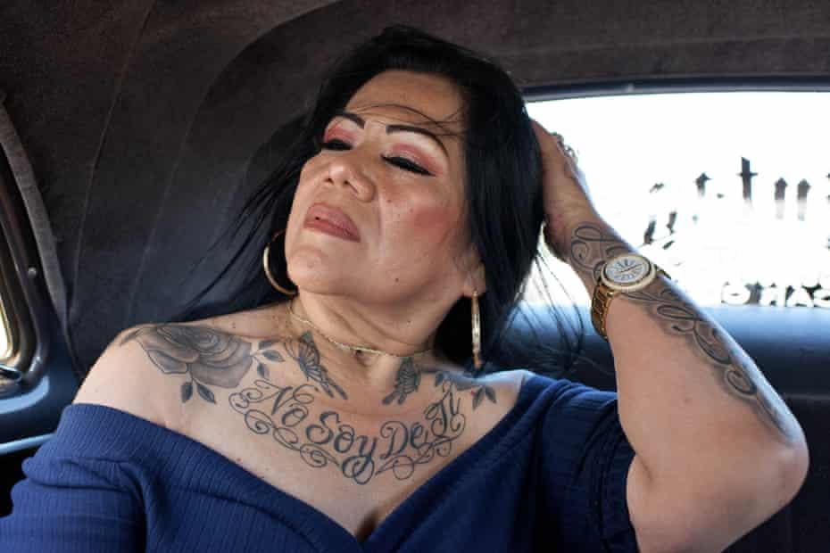 """woman brushes hair back. She has tattoo saying """"No soy de ti"""""""