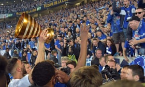 Strasbourg players celebrate with the trophy after winning the cup.