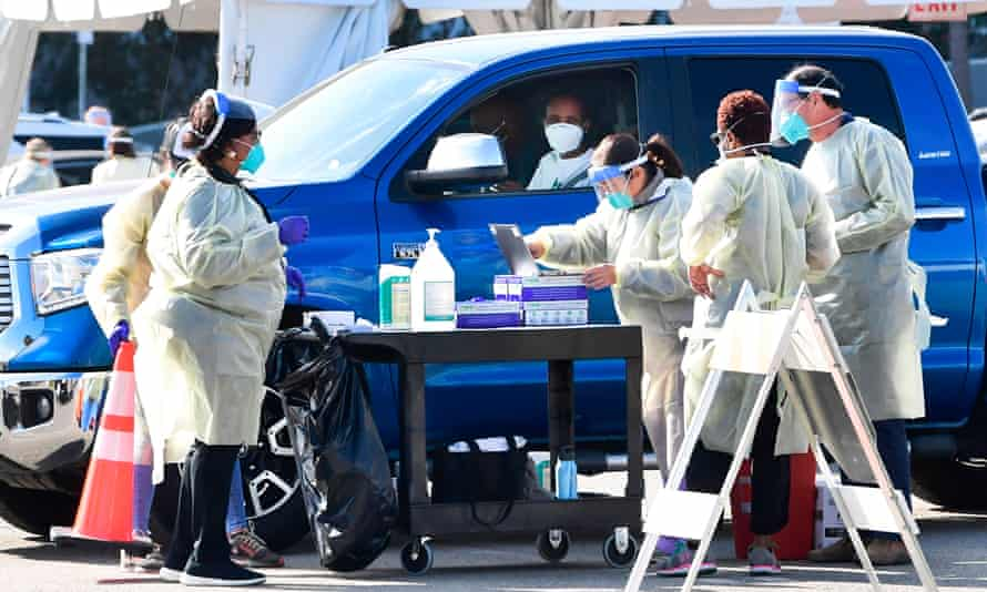 People pull up for Covid-19 vaccines in the parking lot of the Forum in Inglewood, California on 19 January 2021.
