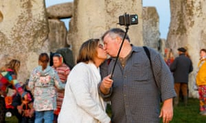 Couple kissing and using a selfie stick in front of stonehenge