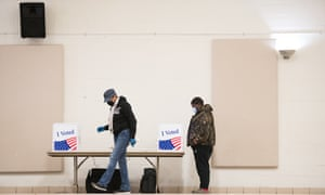 A poll worker walks across the room as a voter looks at their choices in Columbia, South Carolina.