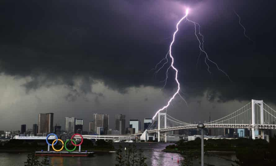A lightning strike in Tokyo near a statue of the Olympic rings