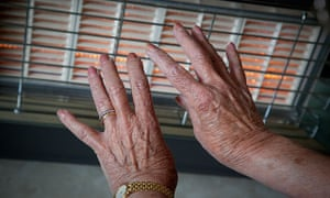 An elderly woman warms her hands by the gas fire