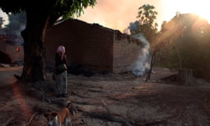 A woman looks at burning houses in the town of Bossangoa, north of Bangui, the Central African Republic's capital