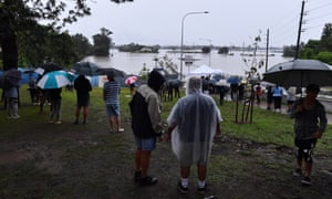 Onlookers watch the submerged New Windsor Bridge at Windsor in the north west of Sydney, Monday, March 22, 2021.