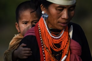 ANaga tribeswoman carrying a child at the end of an overnight ceremony to bless the harvest in Satpalaw Shaung village