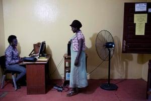 Two registrars stamp and register births at the Kakata Rennie hospital in Margibi, Liberia.
