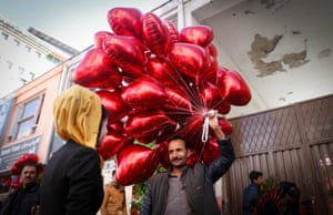 Kabul, Afghanistan. A man sells heart shaped balloons in the street for Valentine's Day