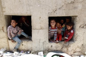 Displaced Yemeni children look out of an underground water tunnel, where they are taking shelter after their houses were destroyed by airstrikes in Sanaa