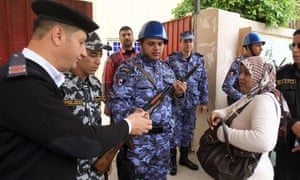 Police officers and armed soldiers check a voter's ID at a polling station in the port city of Alexandria