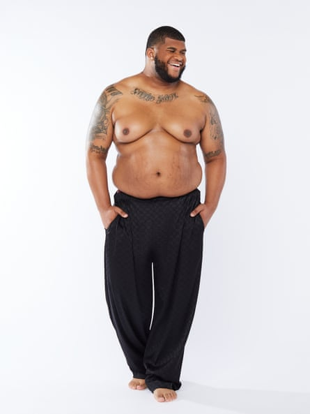 A large, bare-chested Savage x Fenty male model in trousers