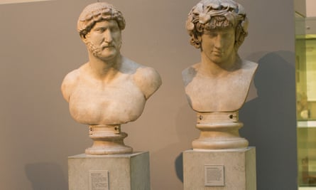 Marble portrait head from a statue of Antinous wearing a wreath of ivy, next to marble bust of Emperor Hadrian.
