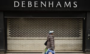 A woman walks past shutters at the entrance to a Debenhams department store in Manchester