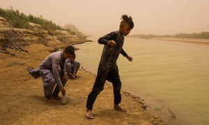 Young boys catch small fish for their families to eat from the Helmand river on the Afghan side of the border with Iran, just outside the city of Zarang, in Afghanistan's Nimroz province.
