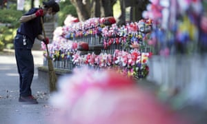 """An employee wearing a protective mask to help curb the spread of the coronavirus sweeps near pinwheels whirl in the breeze at rows of small stone statues of """"jizo"""" representing the unborn children at a temple in Tokyo Thursday, 29 October, 2020."""