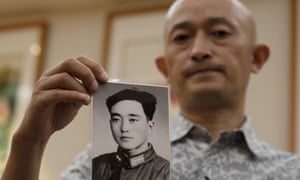 Zhang Hai holds up a photo of his father taken in his youth during an interview in Shenzhen in southern China's Guangdong province
