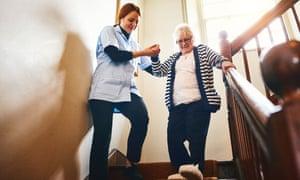 Caregiver helping senior woman walk down stairs