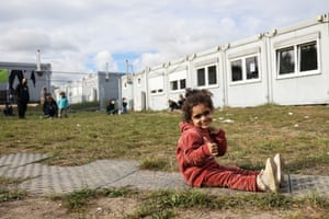 A girl from Iraq poses for a photo next to a holding facility in Eisenhuttenstadt, Germany