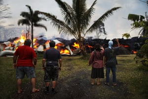 Community members watch as a home is destroyed by lava from a Kilauea volcano.