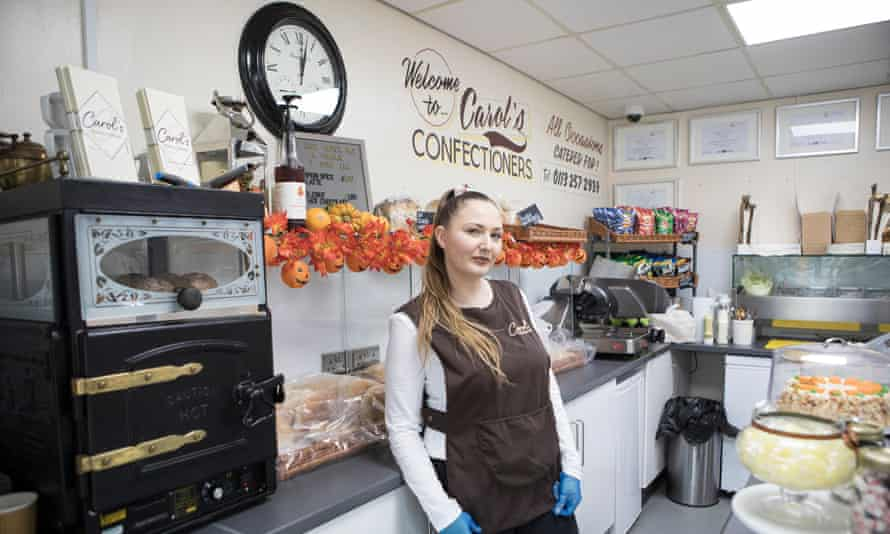 Claire O'Toole standing behind the counter surrounded by food for sale, with a clock and a Carol's Confectioners logo on the wall behind